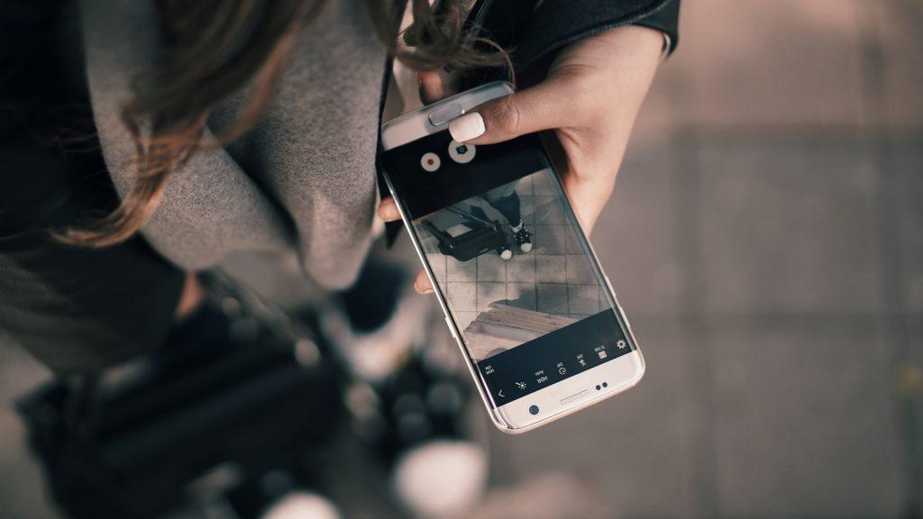 Mão de mulher com telemóvel nas redes sociais