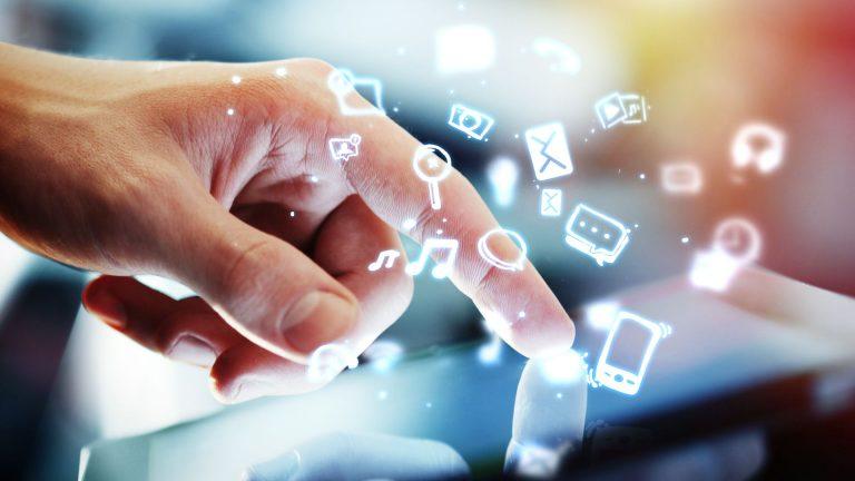 mão num tablet com ícones digitais